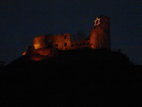 Beautiful castle ruins lit up on the hill above the town